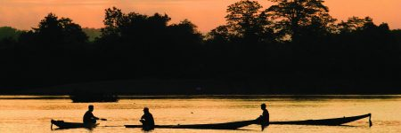 Fischer mit traditionellen Langbooten unterwegs auf dem Mekong Si Phan Don zum Sonnenuntergang