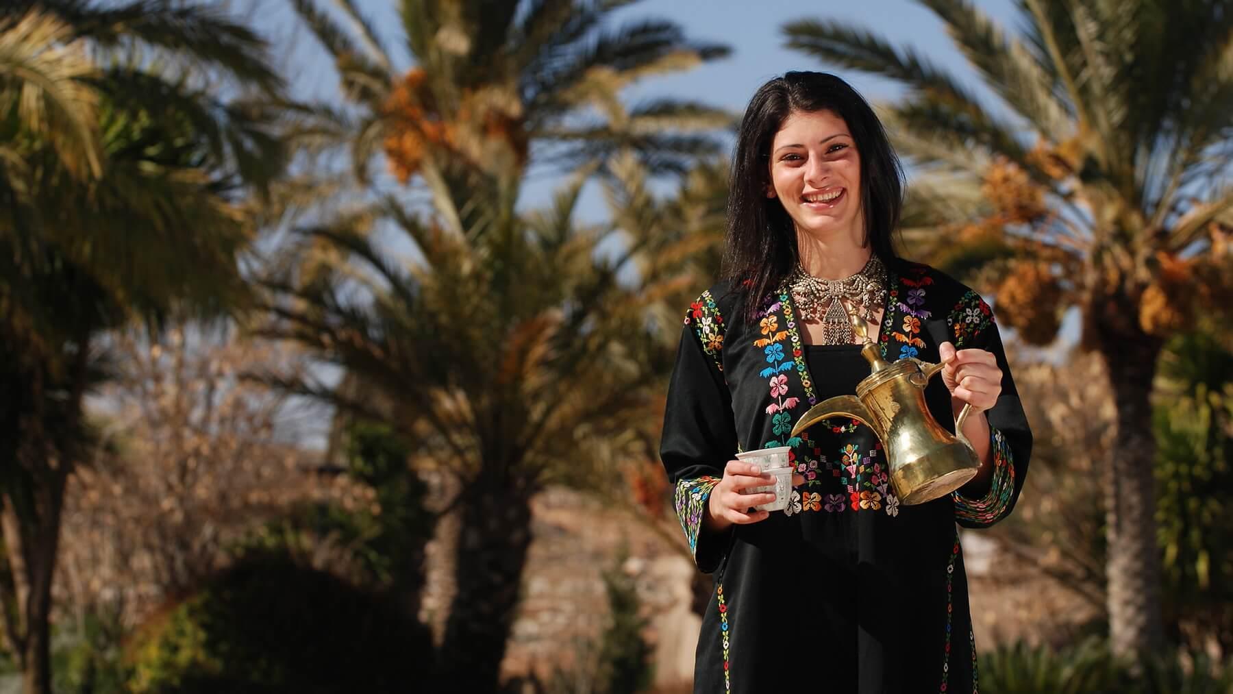Jordaniesche Frau in traditioneller Kleidung schenkt Tee aus Kanne ein.