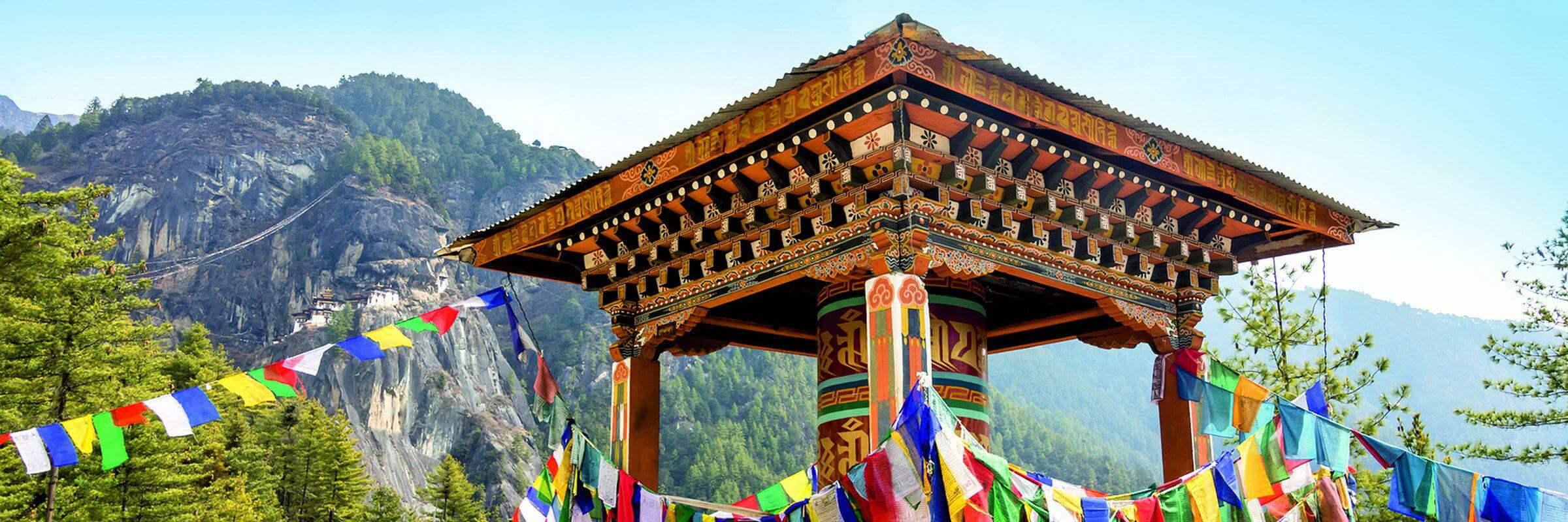 Eine große Gebetsmühle mit vielen Gebetsfahnen auf dem Weg zum berühmten Tigernest, dem Taktshang Kloster