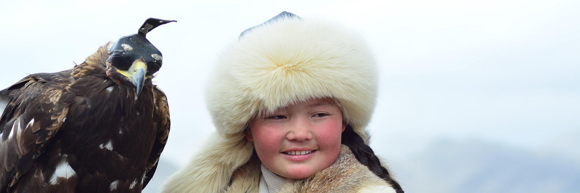"""Junge Gewinnerin der Adlerwettkämpfe beim """"Golden Eagle Festival"""" ein Höhepunkte einer Mongolei Reise"""