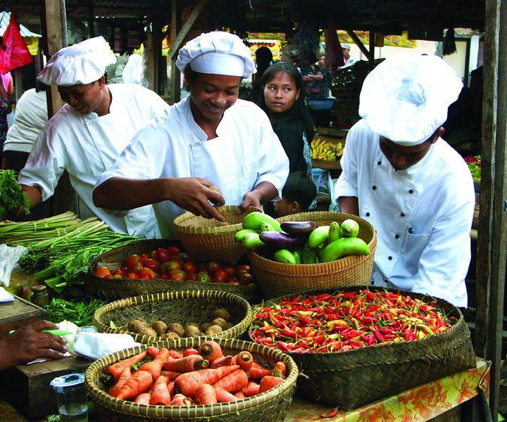 Auf einem bunten Markt auf Bali in Indonesien wird frisches Obst und Gemüse verkauft.