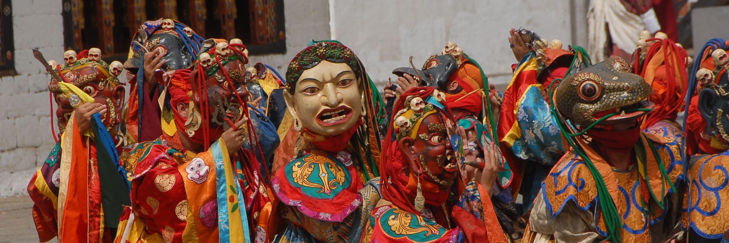 Maskentänzer mit traditionellen Gewändern und Masken bei der Darstellung eines spirituellen buthanesischen Tanzes.