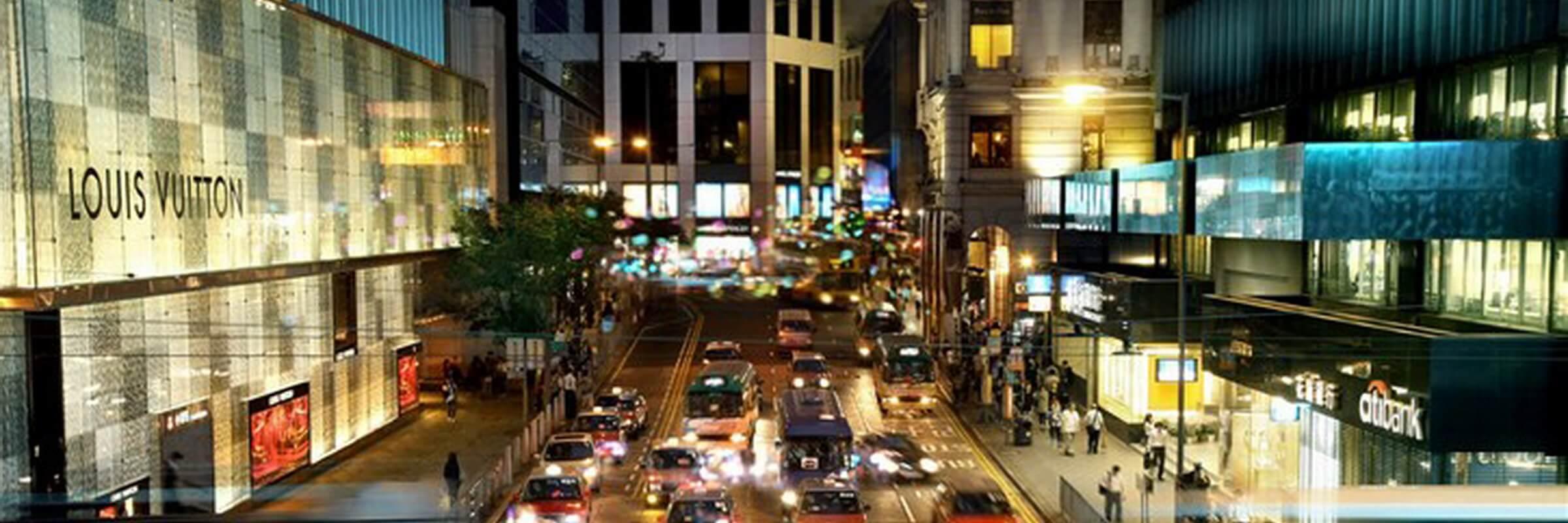 Einkaufsstraße mit Geschäften und Straßenverkehr im Zentrum von Hongkong.