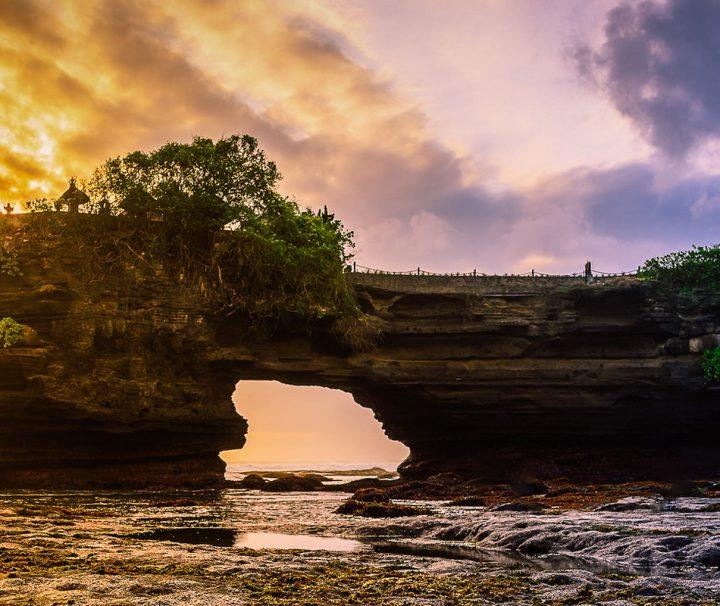"""Auf dem Fußweg ist der """"Meerestempel"""" Pura Tanah Lot nur bei Ebbe über einen 50 m langen Gang über rundgewaschene Steine zu erreichen."""