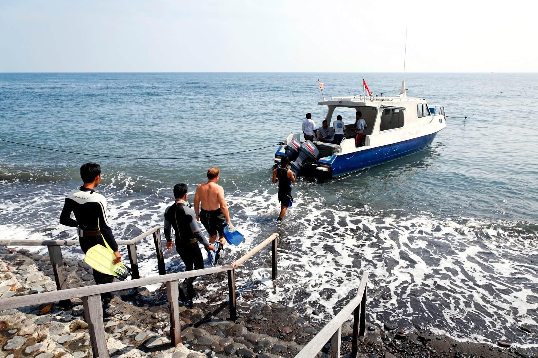 Urlauber brechen mit einem Tauchboot zu einem Tauchausflug in den Gewässern nahe des Alam Anda Ocean Front Resort & Spa auf.