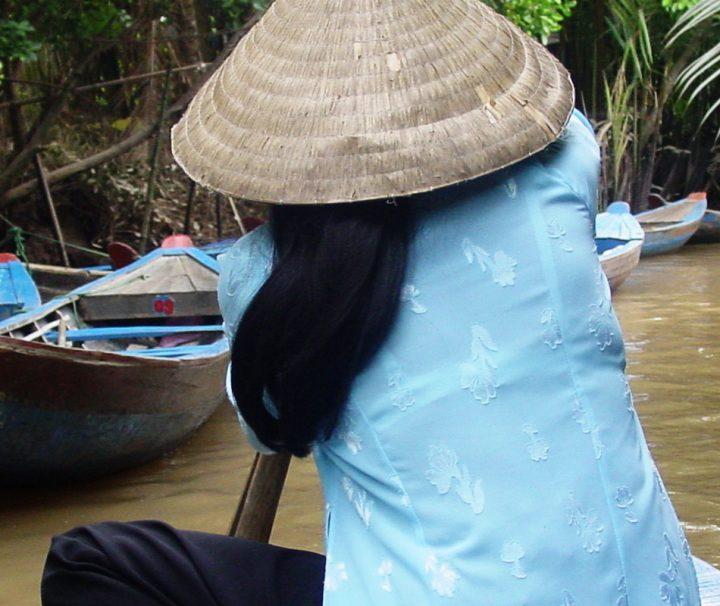Einheimische Frau bei einer Fahrt auf einem kleinen Seitenarm des Mekongs, Erleben Sie den Mekong auf unserem Vietnam Rundreisen