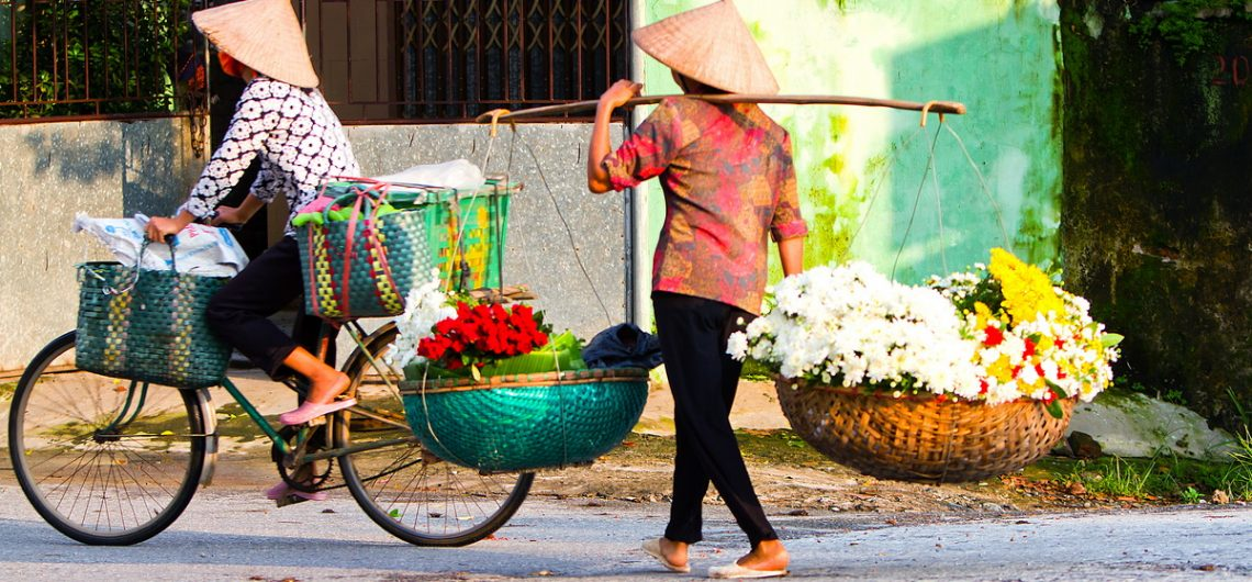 Blumenverkäuferinnen durchstreifen die Straßen im vietnamesischen Hanoi