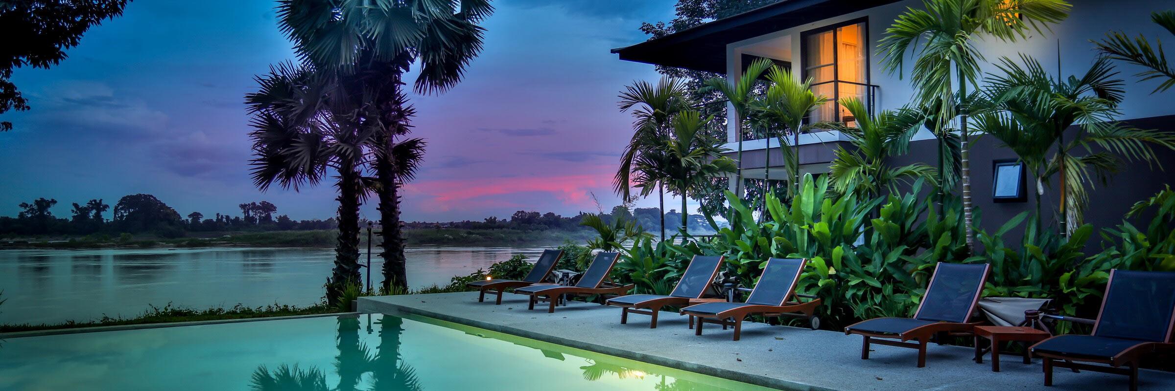 Infinity-Pool mit Sonnenterasse bei Sonnenuntergang im Herzen des River Resort Champasak
