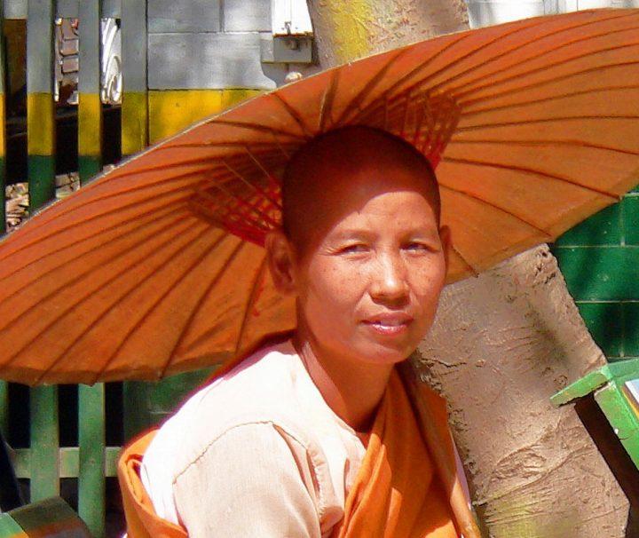 Novizin mit Sonnenschirm auf einer Parkbank in Mandalay Myanmar sitzend
