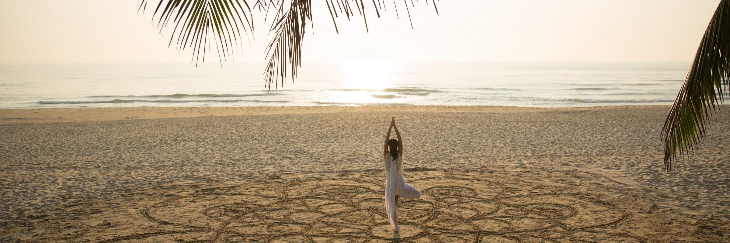 Yogaübungen am Hotelstrand im Fusion Maia Danang Resort mit Panoramablick auf das Meer, eine entspannte Weise den Vietnam Urlaub zu gestalten.ramablick auf das Meer