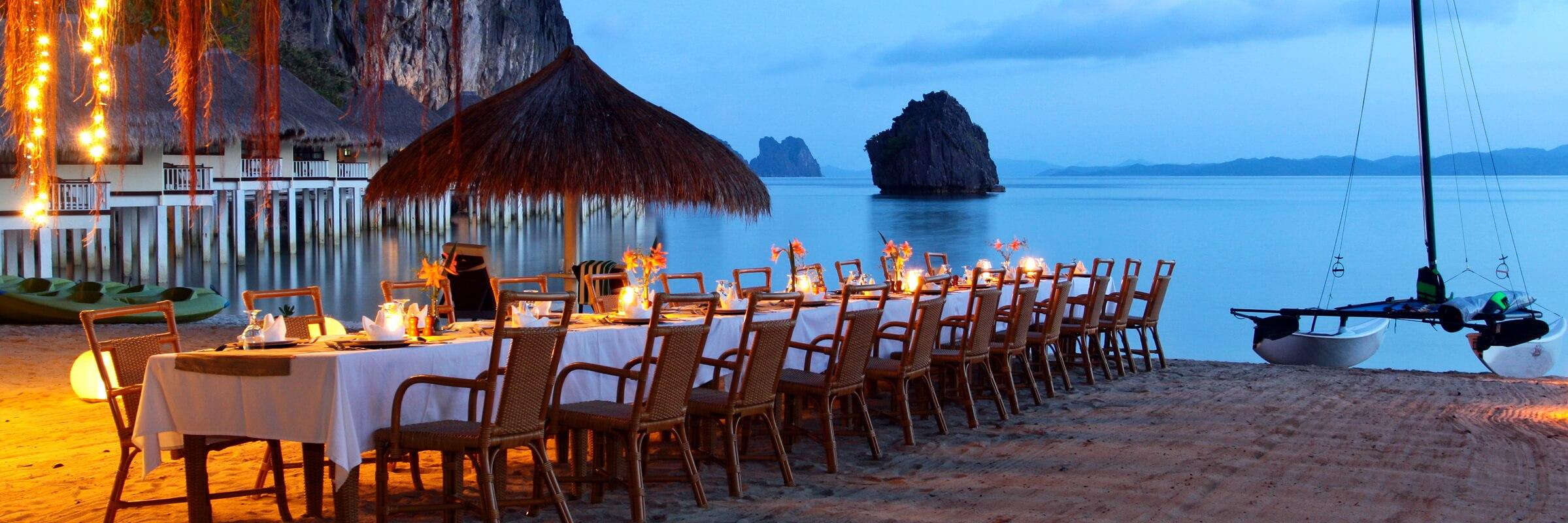 Ein Gemütliches Dinner am Strand im El Nido Apulit Island Resort bei Sonnenuntergang