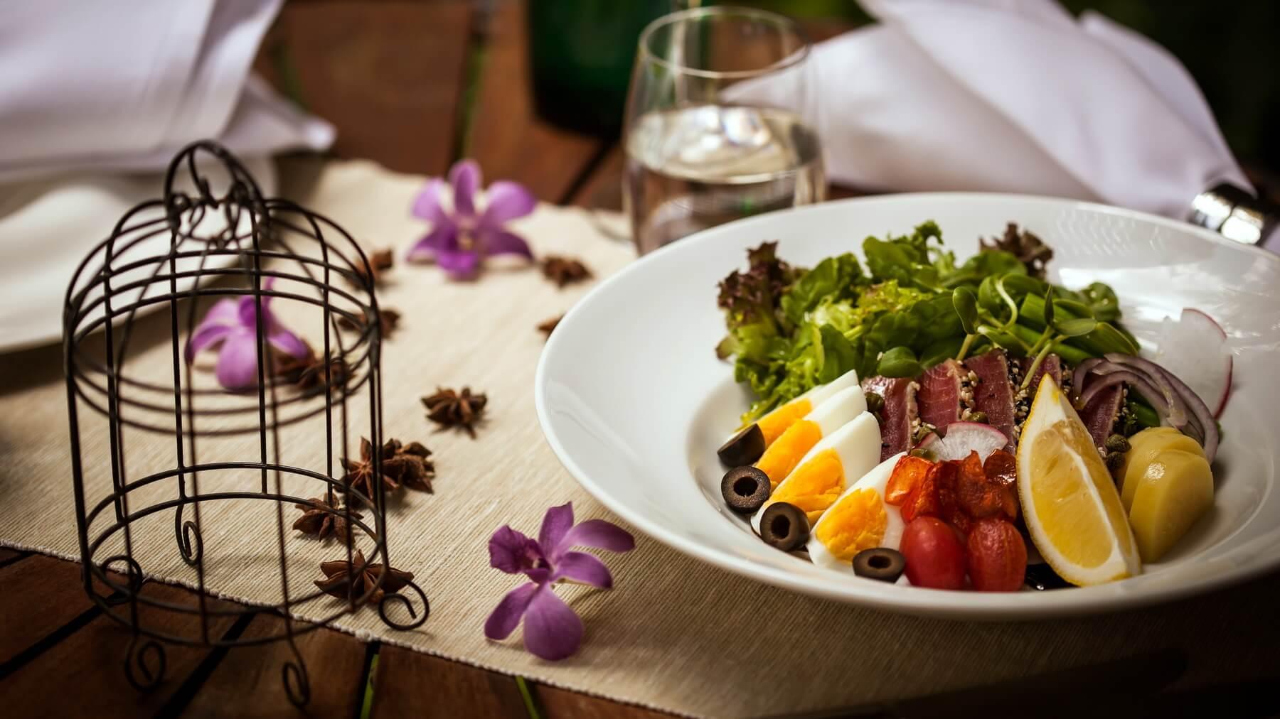 Eingedeckter Tisch mit serviertem Salatteller im Restaurant des Peace Resorts Koh Samui in Thailand.