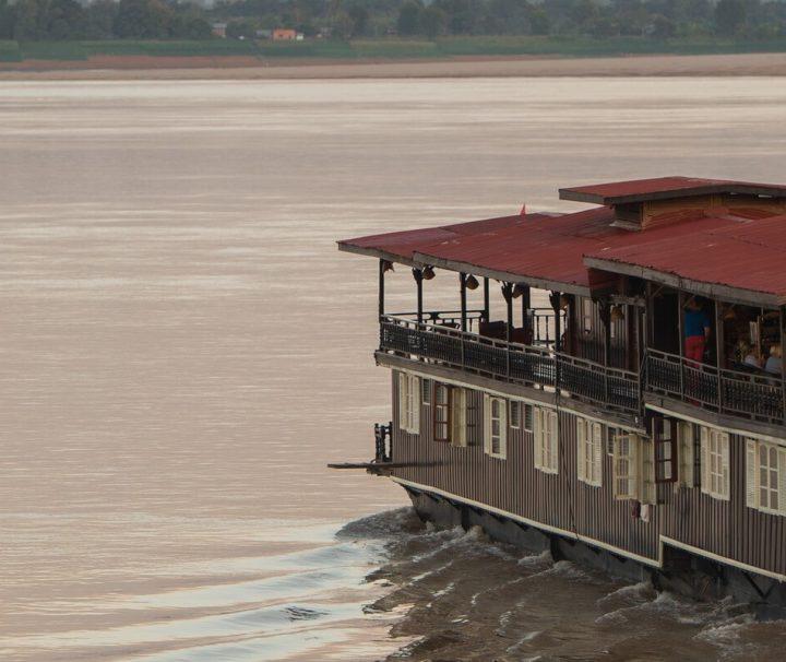 Auf einer Kreuzfahrt mit der Vat Phou können Gäste bei einem Sundowner in der Bar einen atemberaubenden Sonnenuntergang genießen.