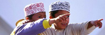 Zwei Jungen in traditioneller omanischer Kleidung, dem Kumma und Dishdasha.