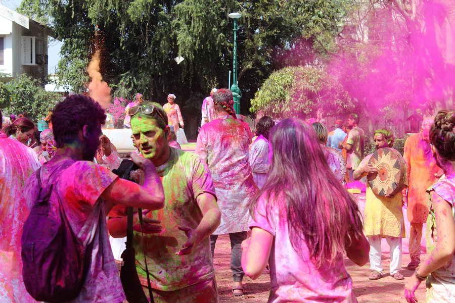 Klassisches Bild während des Holi Festes in Indien: bunte Menschen und Farbe die durch die Luft fliegt