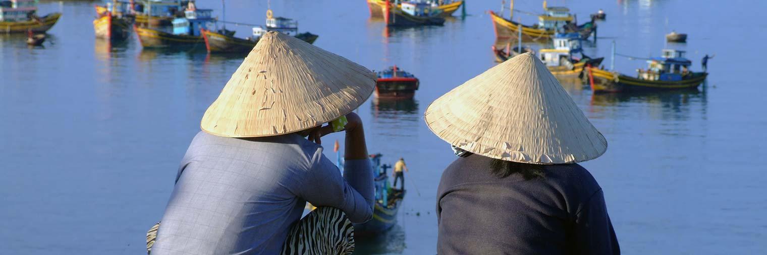 Zwei Einheimische beobachten den lebhaften Bootsverkehr an der Küste von Vietnam.