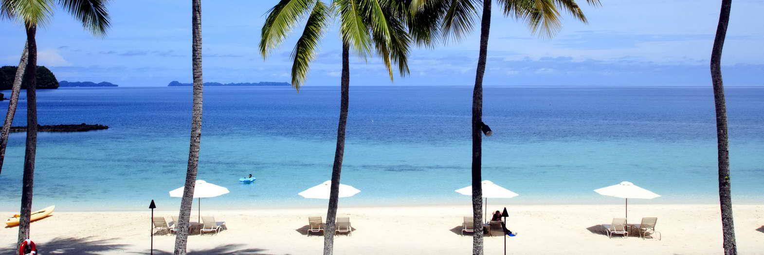 Am palmengesäumten Strandabschnitt des Palau Pacific Resorts finden Ruhesuchende ein schattiges Plätzchen.