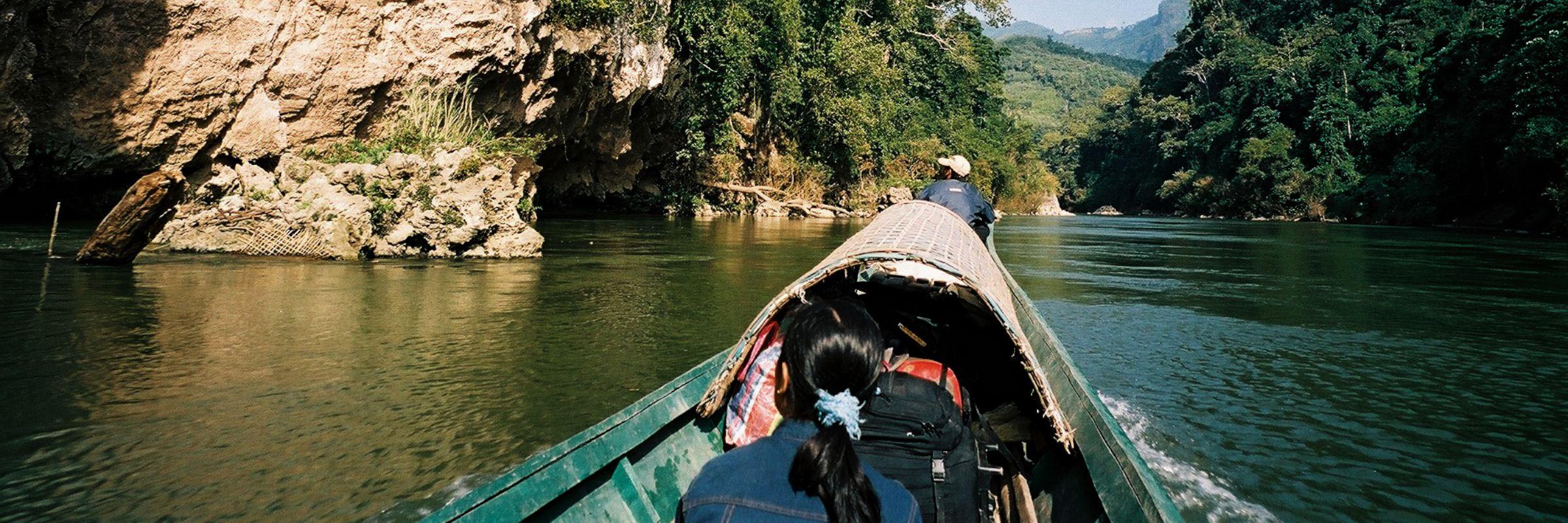 Zwei Einheimische fahren mit einem landestypischen Boot durch eine idyllische Flusslandschaft im Norden von Laos.