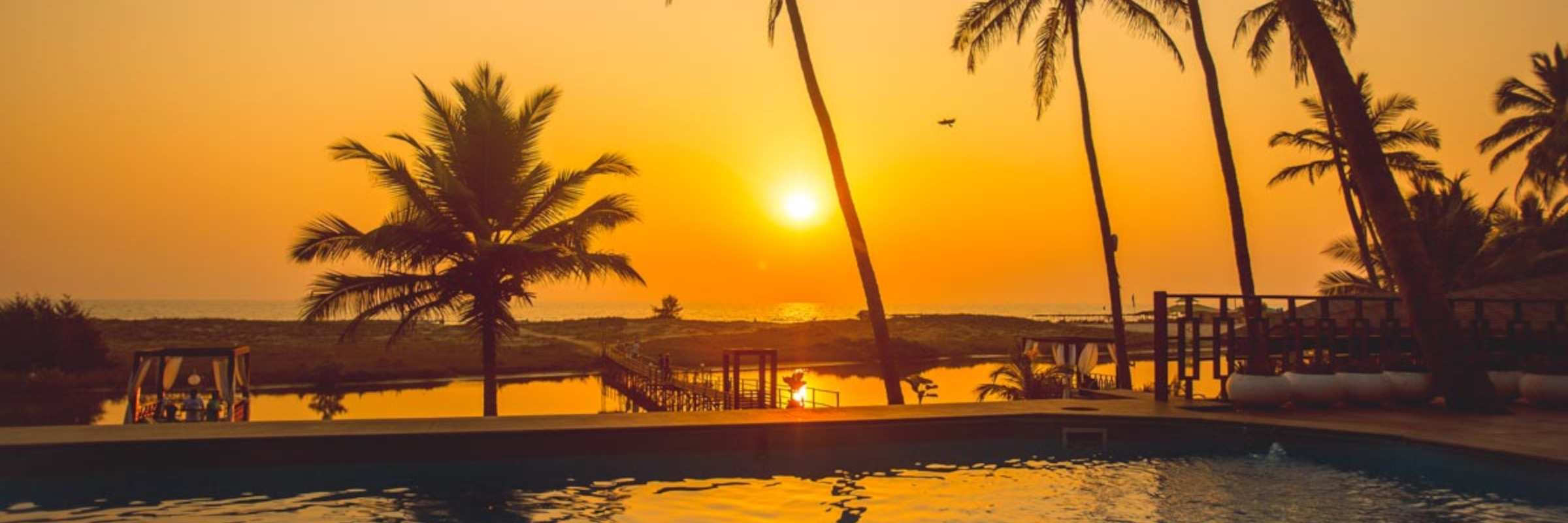 Der im Garten gelegene Außenpool des Riva Beach Resort mit Liegestühlen bietet einen hervorragenden Blick auf den abendlichen Sonnenuntergang.